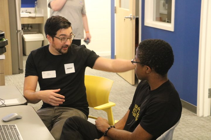A BOSE employee talks with a youth while visiting The Flagship Clubhouse in Roxbury, MA, USA.